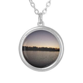 Fishing poles silhouette against the sun set round pendant necklace